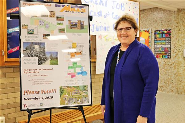 superintendent with capital project poster
